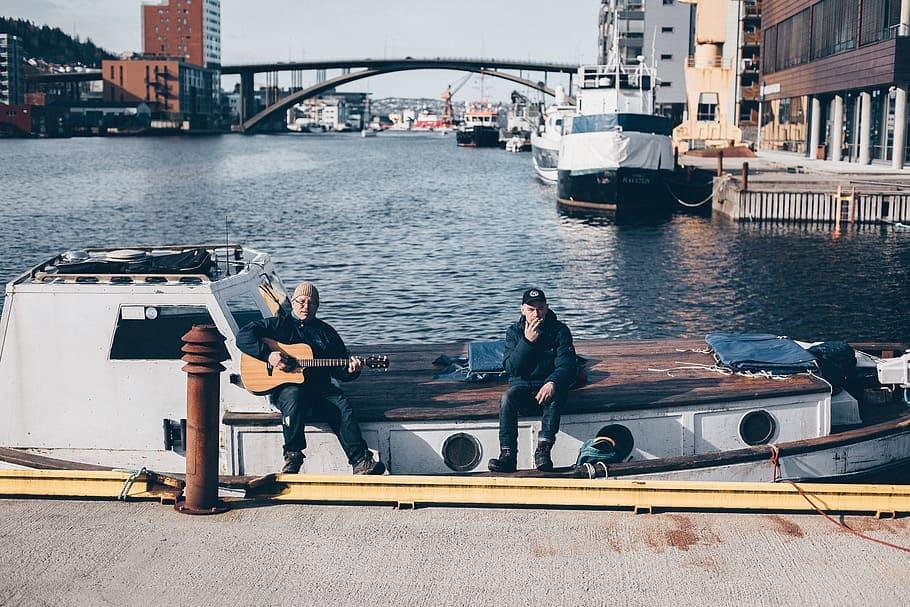 men-sitting-while-playing-guitar-on-boat-at-dock-during-daytime