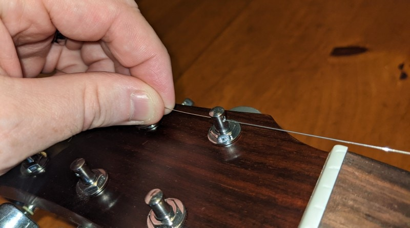 How to Restring an Acoustic Guitar - place loose end into tuning post